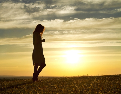 bigstock-Woman-walking-alone-at-sunset-52945624